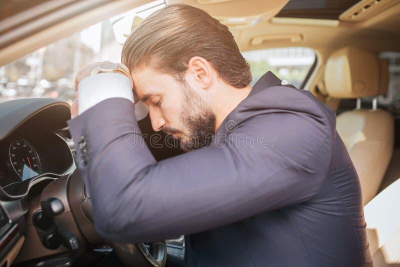 El hombre de negocios joven cansado y agotado se sienta en el coche y se inclina al volante Él mantiene ojos cerrados El dormir d imagenes de archivo