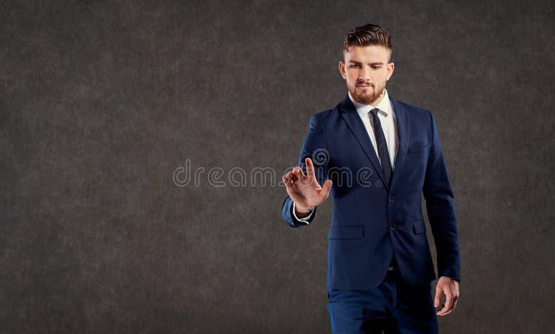 El hombre de negocios joven con una barba hace clic en un punto foto de archivo