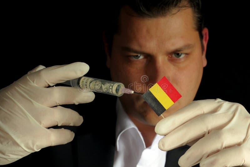 El hombre de negocios joven da una inyección financiera a la bandera belga es fotos de archivo libres de regalías