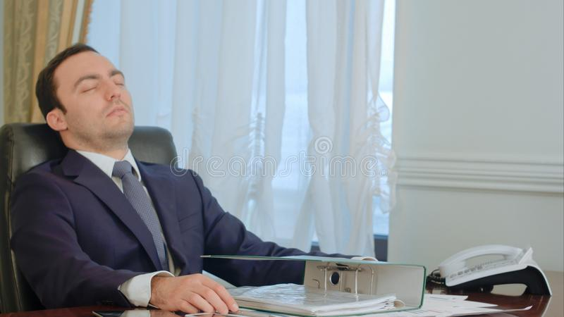 El hombre de negocios joven durmiente despertó por llamada de teléfono en oficina fotos de archivo