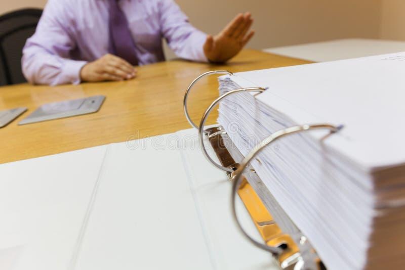 El hombre de negocios joven en la oficina que se sienta delante de la basura de la carpeta para trabajar rechazos ofrece el foco  imagenes de archivo