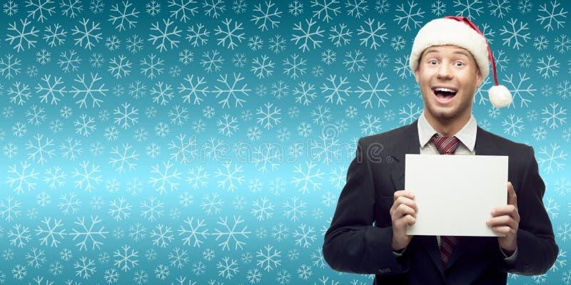 El hombre de negocios joven en la tenencia del sombrero de santa firma encima backgro del invierno fotografía de archivo