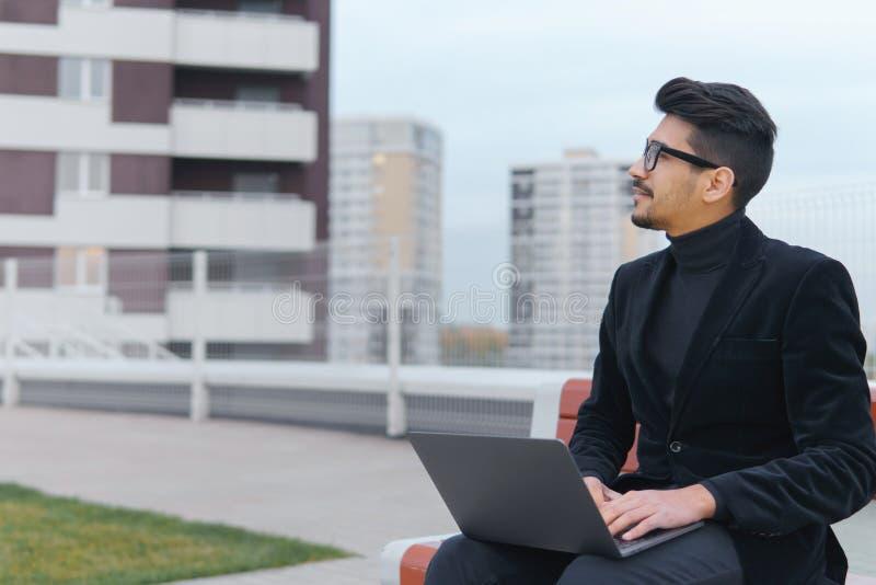 El hombre de negocios joven en lentes trabaja en la sentada del ordenador portátil aventaja fotografía de archivo