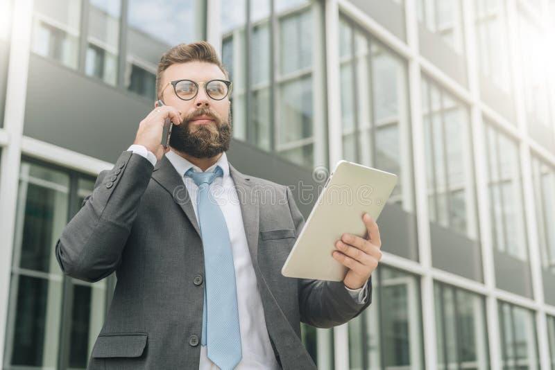 El hombre de negocios joven en traje y lazo se está colocando al aire libre, está sosteniendo la tableta y está hablando en su te fotos de archivo libres de regalías