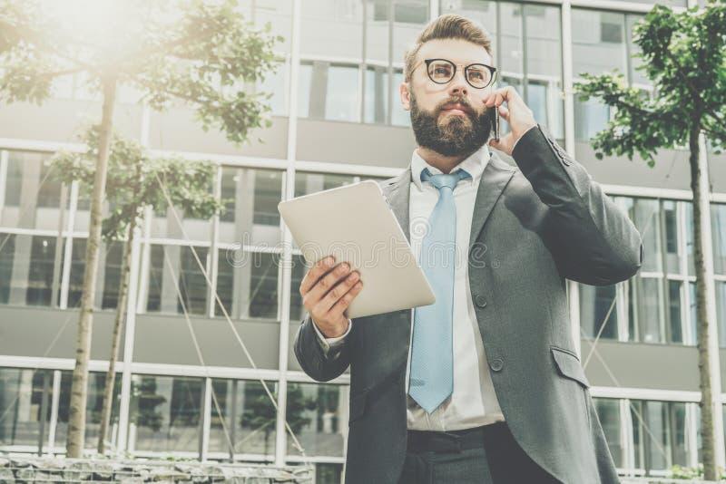 El hombre de negocios joven en traje y lazo se está colocando al aire libre, está sosteniendo la tableta y está hablando en su te imagen de archivo