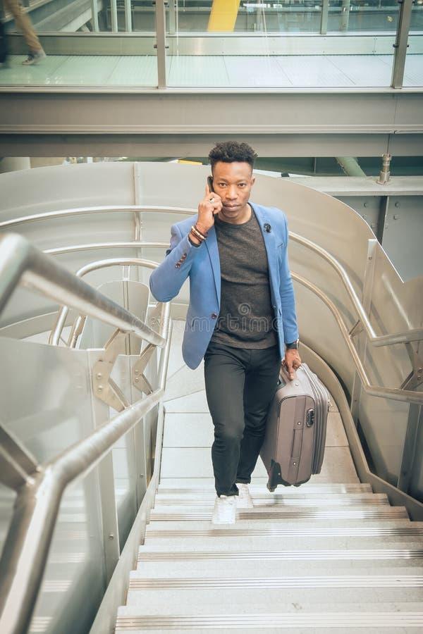 El hombre de negocios joven está subiendo las escaleras en el aeropuerto que habla por t imagenes de archivo