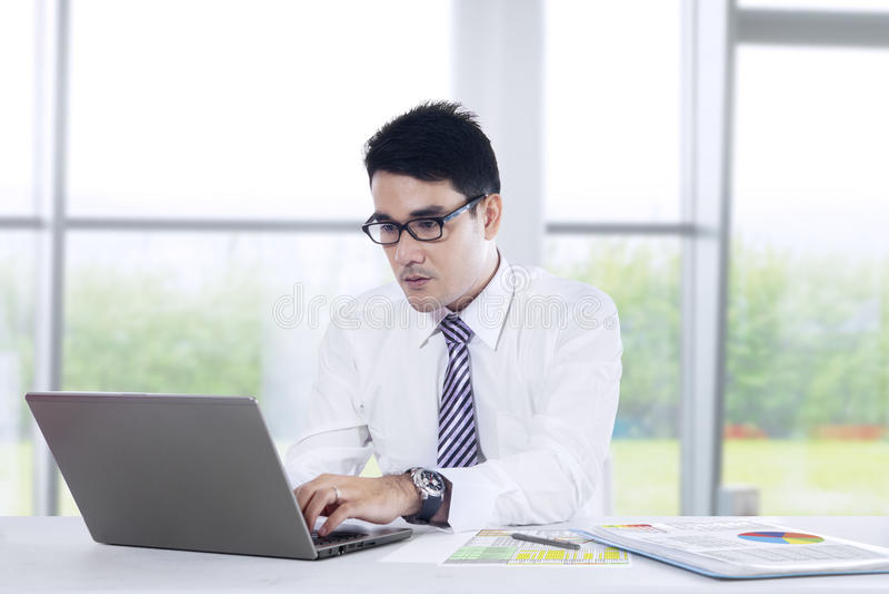 El hombre de negocios joven está trabajando en la oficina fotos de archivo libres de regalías