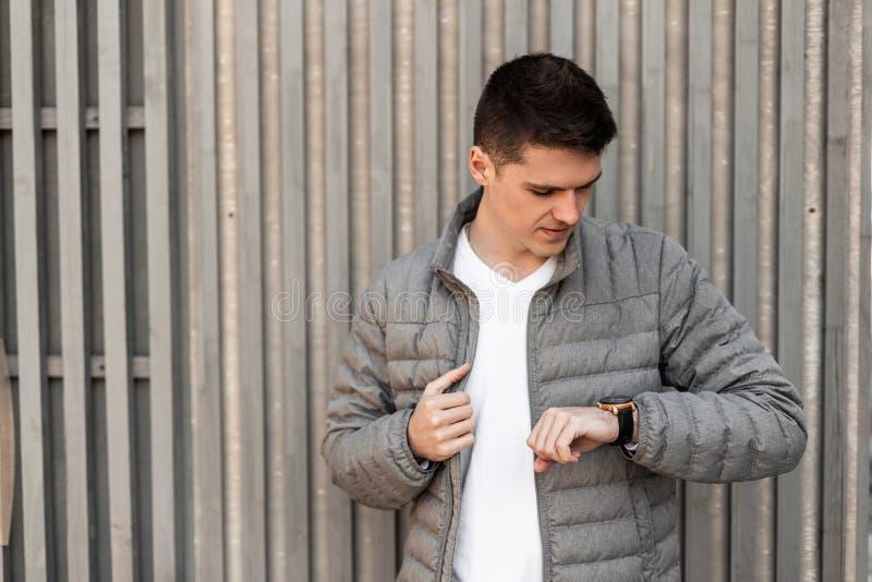 El hombre de negocios joven europeo hermoso en una chaqueta gris de la primavera en una camiseta blanca elegante mira el reloj qu foto de archivo libre de regalías