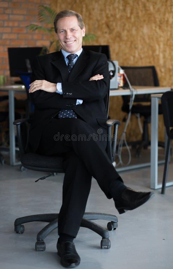 El hombre de negocios joven feliz con las manos cruzó sentarse en una silla encendido fotografía de archivo