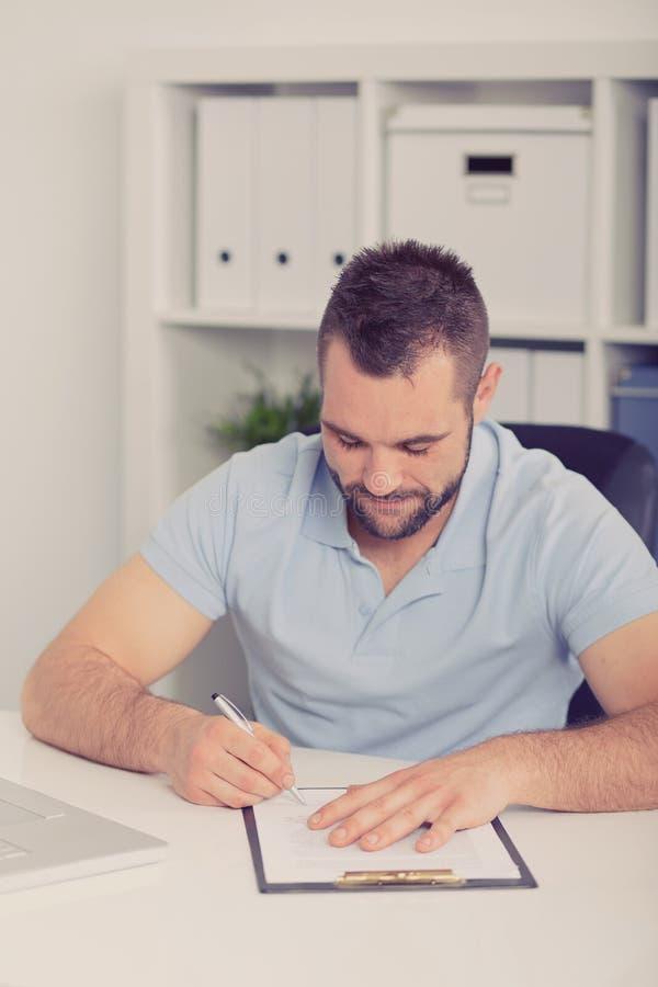 El hombre de negocios joven firma un contrato, entonado foto de archivo
