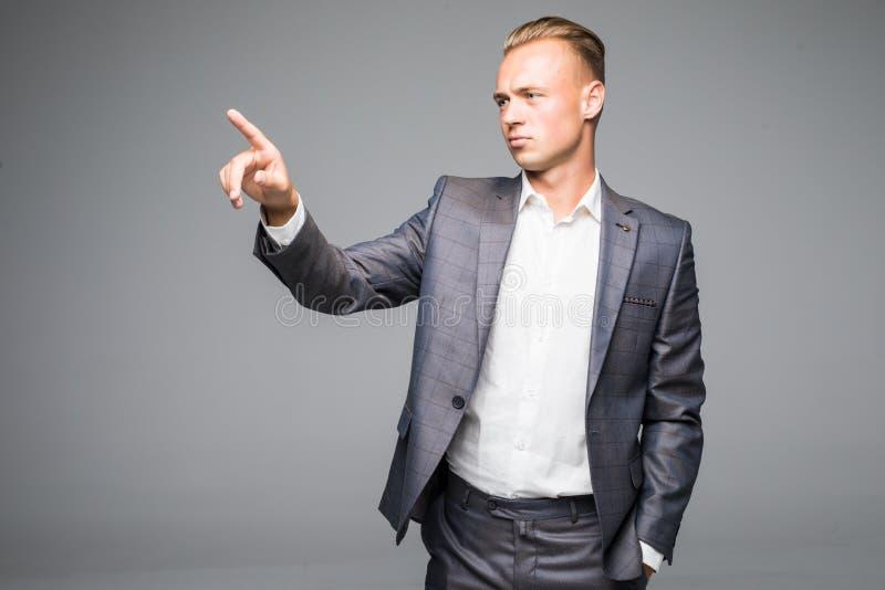 El hombre de negocios joven hermoso empuja el botón invisible en un fondo gris fotos de archivo libres de regalías