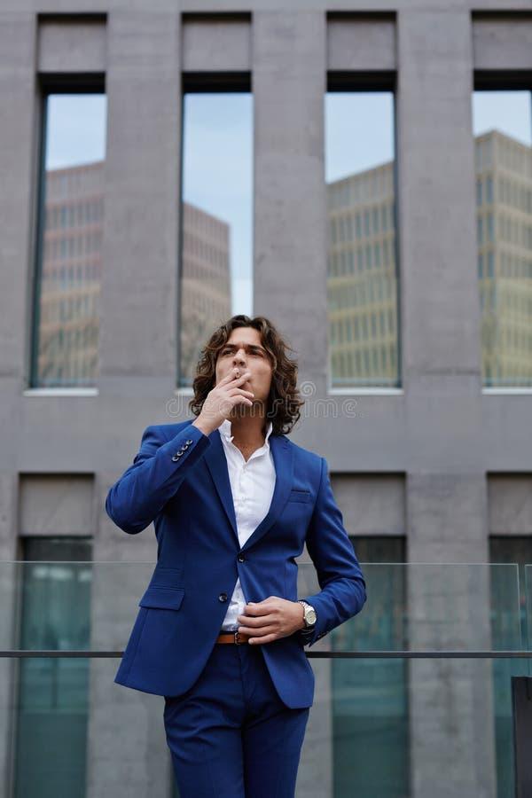 El hombre de negocios joven hermoso en traje elegante fue a la terraza de su oficina a descansar y a tener un cigarrillo foto de archivo libre de regalías