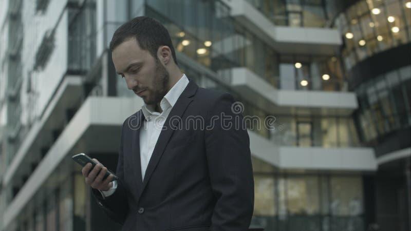 El hombre de negocios joven lee un mensaje de texto derecho fuera de la oficina fotos de archivo