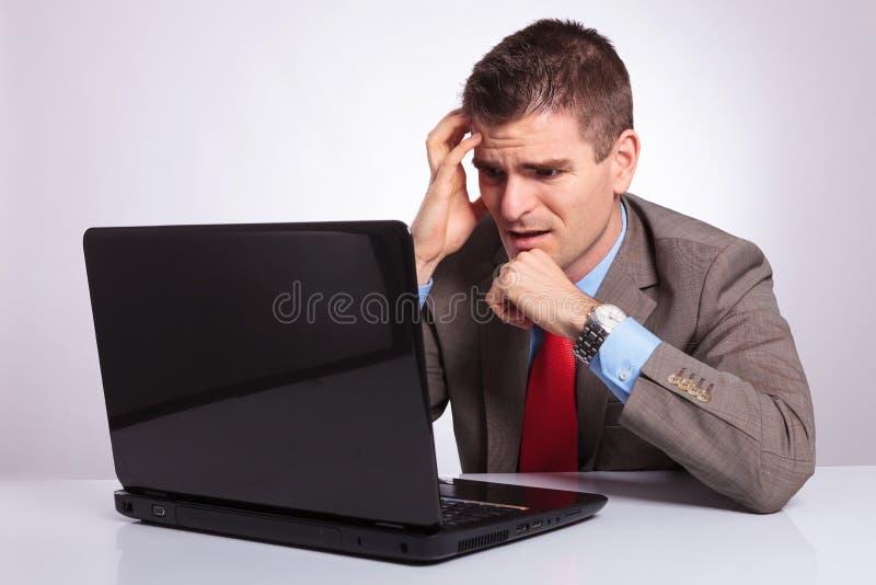El hombre de negocios joven mira decepcionado el ordenador portátil fotografía de archivo