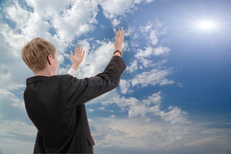 El hombre de negocios joven pide del sol del éxito. imagenes de archivo