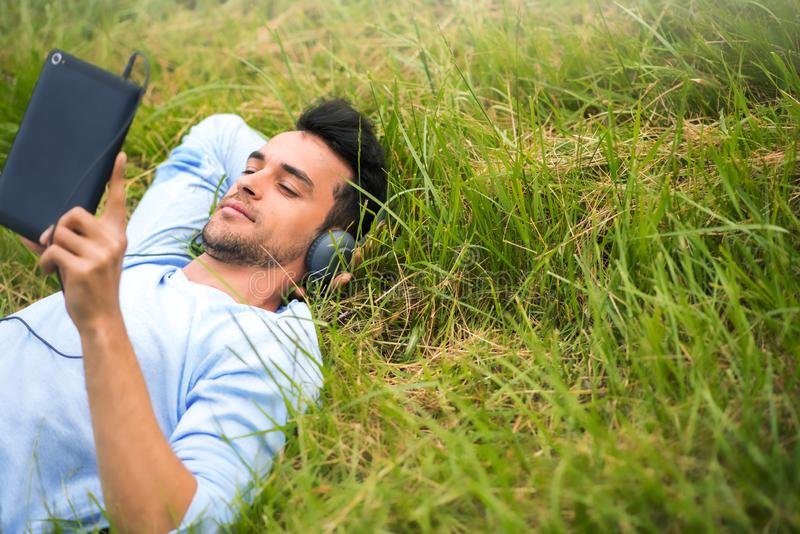 El hombre de negocios joven que miente en la hierba verde escucha música, se relaja con el dispositivo imágenes de archivo libres de regalías
