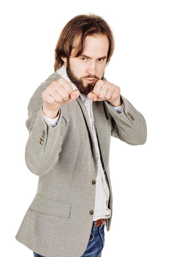 El hombre de negocios joven que se coloca en la posición del boxeador y alista para luchar imagenes de archivo
