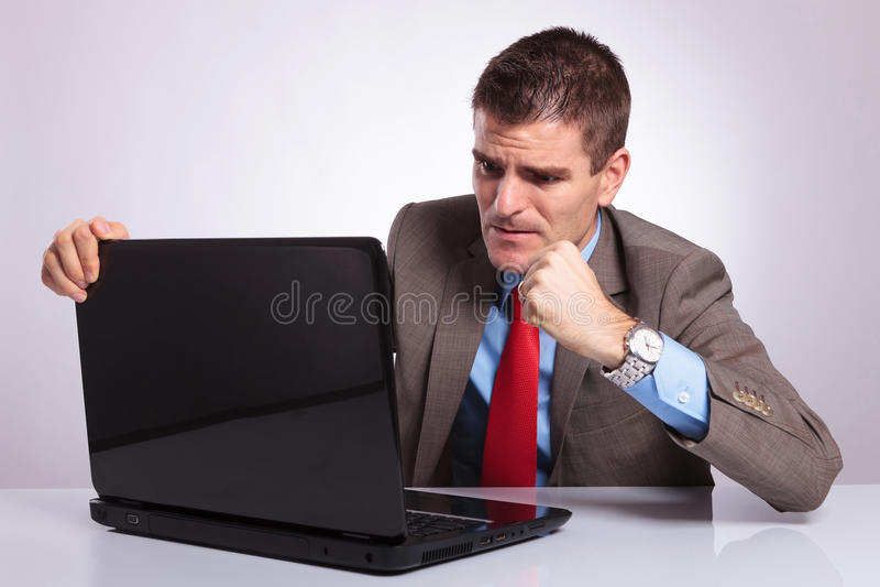 El hombre de negocios joven quiere perforar el ordenador portátil imagen de archivo