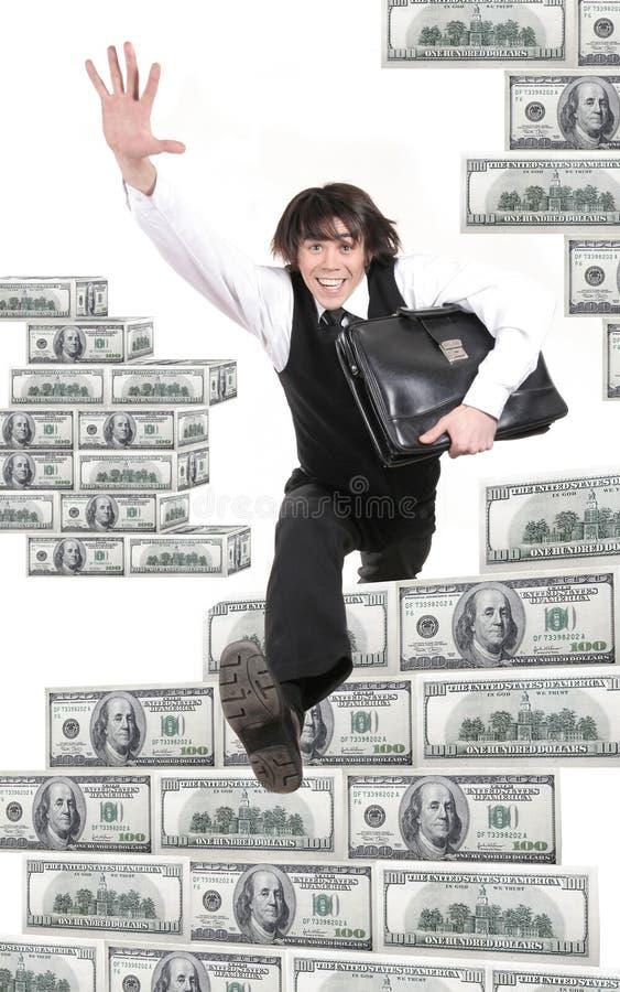 El hombre de negocios joven salta a través de dólares foto de archivo libre de regalías