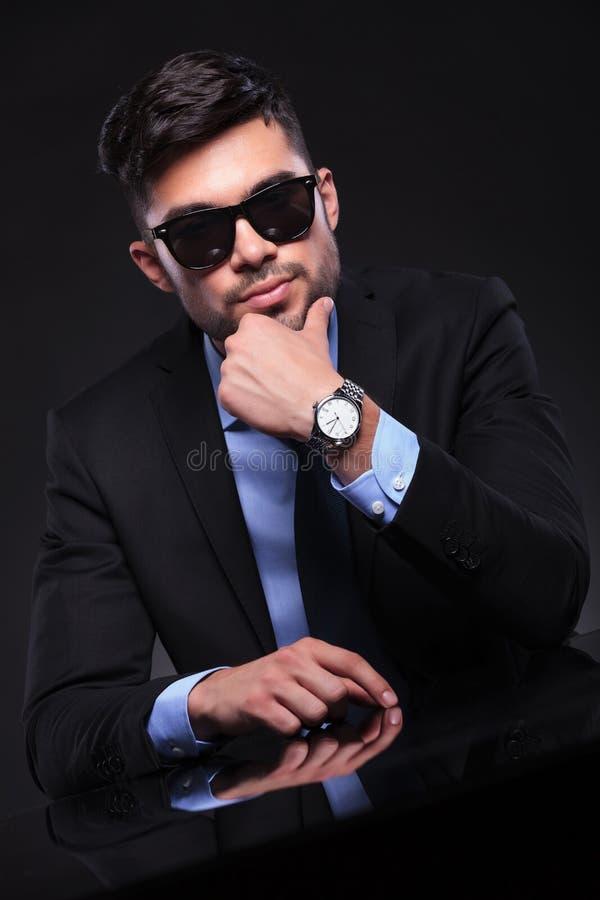El hombre de negocios joven se coloca con la mano en la barbilla en el escritorio foto de archivo