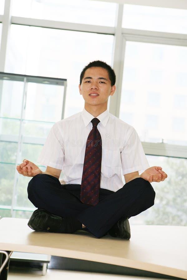 El hombre de negocios joven se sienta en oficina imagenes de archivo