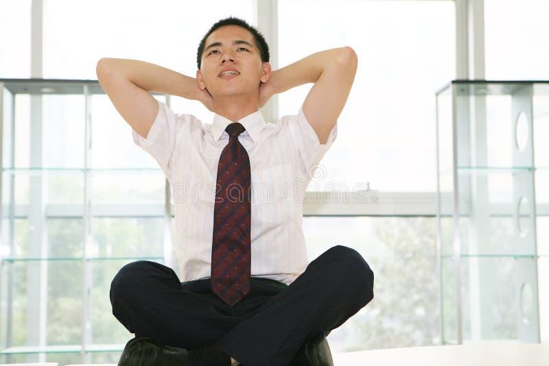 El hombre de negocios joven se sienta en oficina foto de archivo libre de regalías