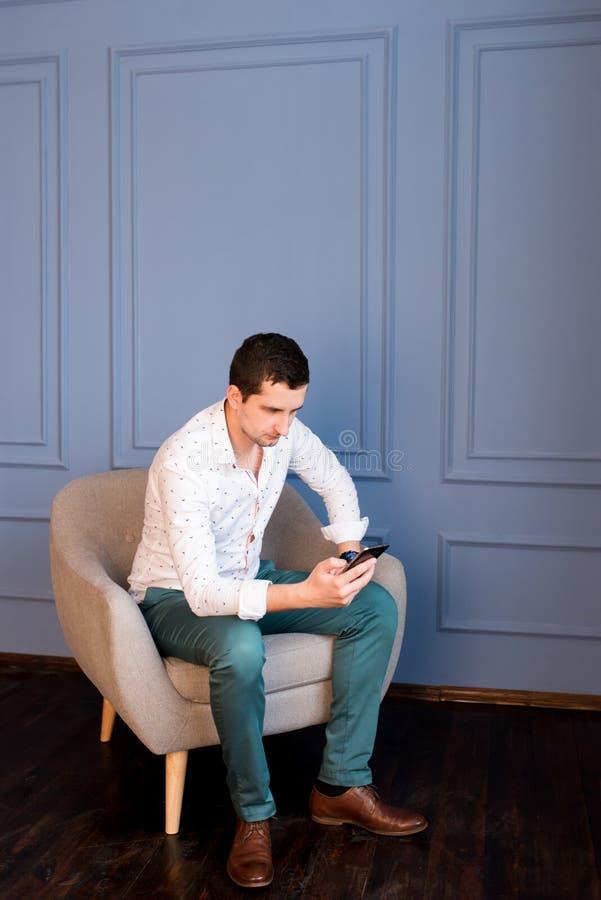 El hombre de negocios joven serio escribe mensajes en su smartphone que se sienta en butaca imagen de archivo