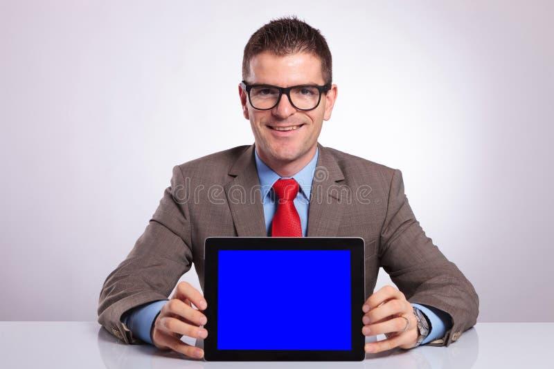 El hombre de negocios joven sostiene una tableta en su escritorio fotos de archivo libres de regalías