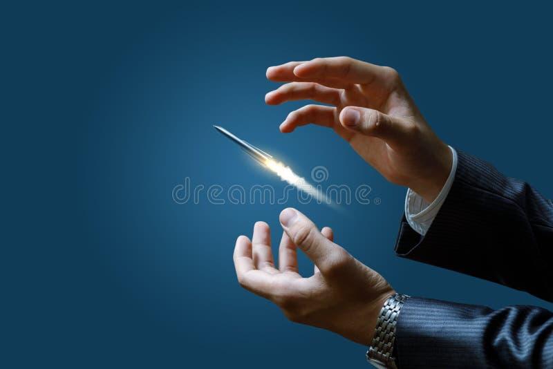 El hombre de negocios lanza un misil en un fondo azul imagenes de archivo