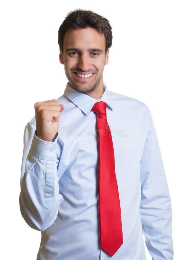 El hombre de negocios latino con el lazo rojo es feliz imagenes de archivo