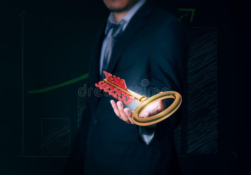 El hombre de negocios lleva a cabo el éxito dominante del equipo disponible en fondo fotos de archivo libres de regalías