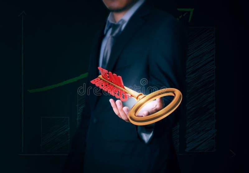 El hombre de negocios lleva a cabo el negocio dominante del equipo disponible en fondo imagen de archivo libre de regalías