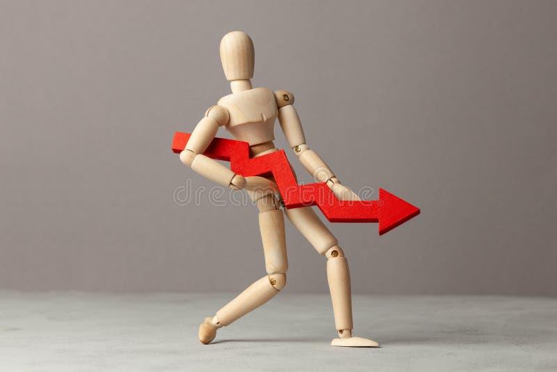 El hombre de negocios lleva a cabo la carta roja de la flecha del plumón Descenso en rentabilidad o quiebra, disminución en renta imagenes de archivo