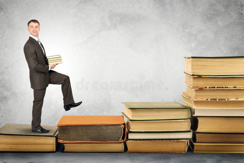 El hombre de negocios lleva la pila de libros y de paseos para arriba imagen de archivo libre de regalías