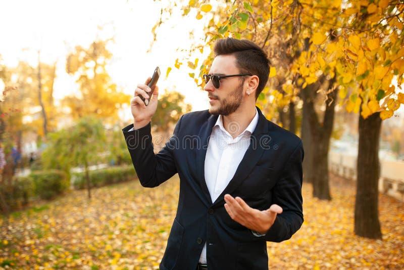 El hombre de negocios masculino elegante joven hermoso muy sorprendió por llamada de teléfono desagradable imagenes de archivo