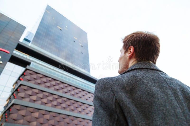 El hombre de negocios masculino joven está soñando Visión desde detrás del hombre de la parte inferior hasta el edificio de ofici imagen de archivo