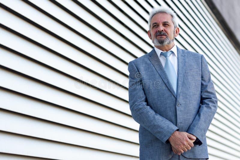 El hombre de negocios mayor con los brazos cruzó fuera de los BU modernos de la oficina foto de archivo