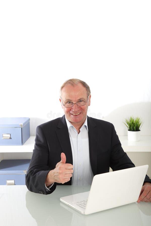 El hombre de negocios mayor que da los pulgares sube gesto foto de archivo