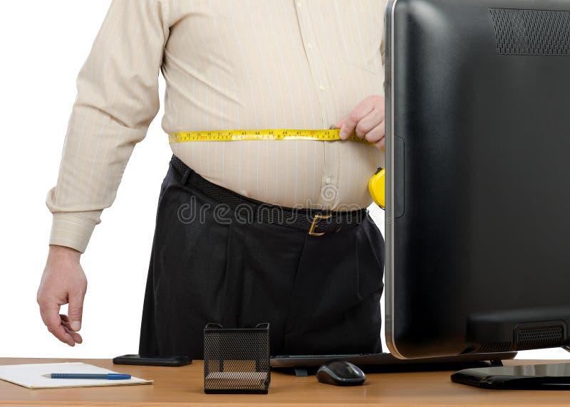 El hombre de negocios mide la cintura grande por el metro de la cinta fotografía de archivo