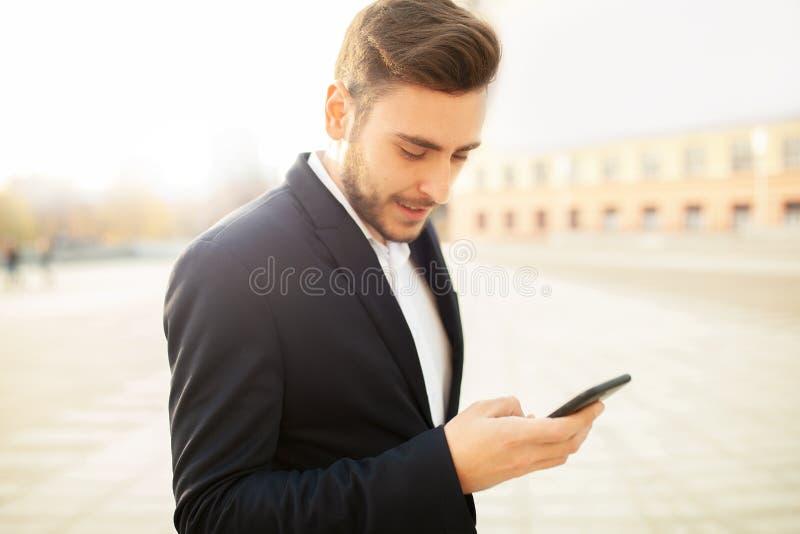 El hombre de negocios milenario mira en la pantalla de su teléfono móvil fotografía de archivo