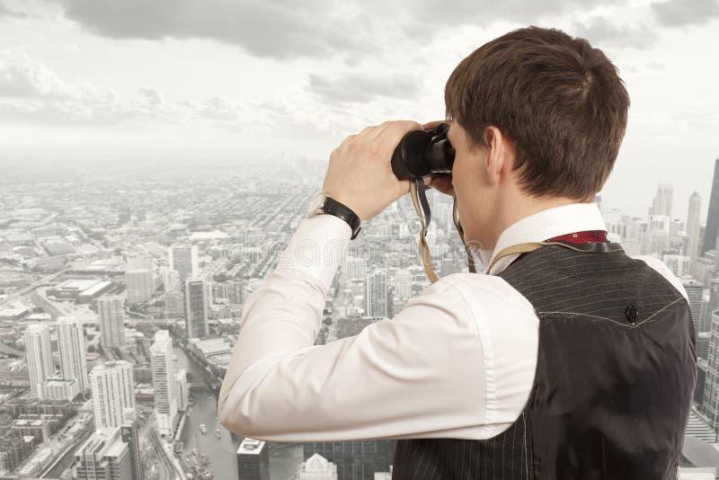 El hombre de negocios mira con los prismáticos imagenes de archivo