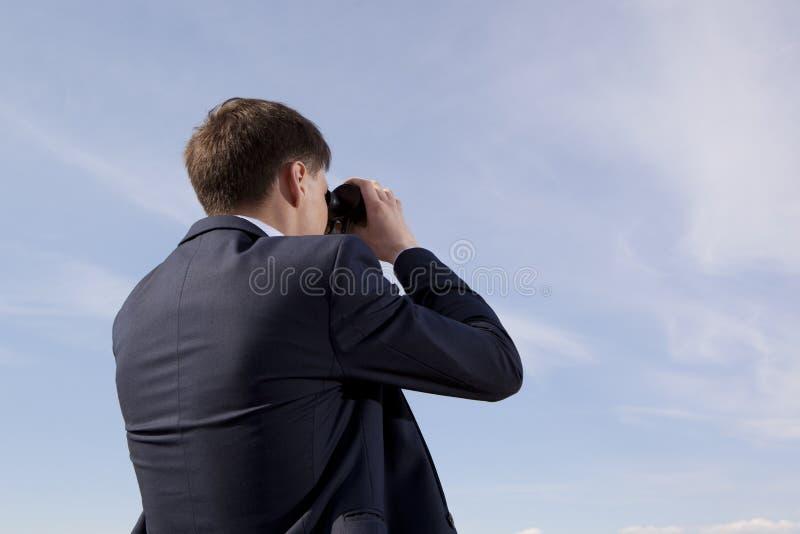 El hombre de negocios mira con los prismáticos fotografía de archivo libre de regalías