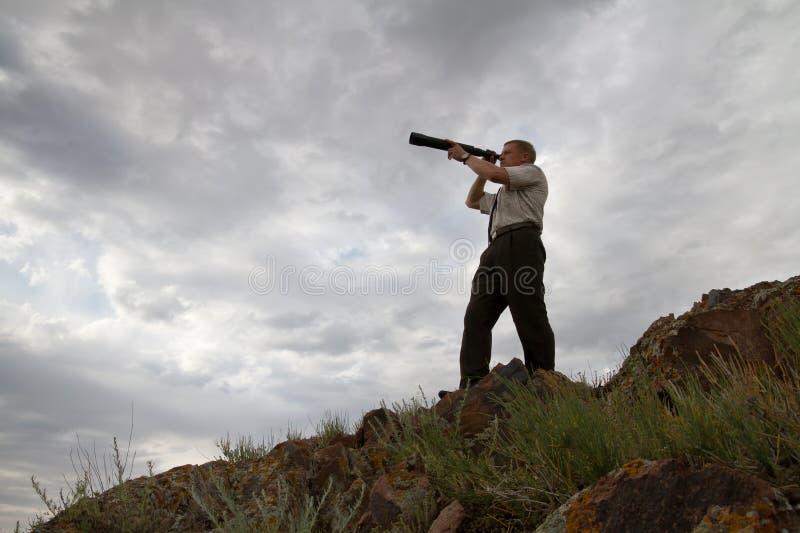 El hombre de negocios mira en un telescopio imagen de archivo libre de regalías