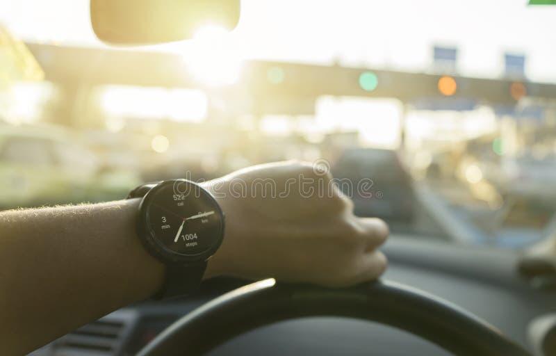 El hombre de negocios mira el smartwatch que muestra de distancia del cálculo el podómetro de las calorías por día en coche con l foto de archivo libre de regalías