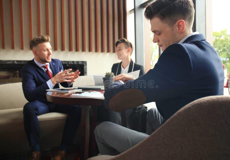 El hombre de negocios mira su reloj que comprueba el tiempo Empresario que sienta una reunión y un funcionamiento en el fondo foto de archivo libre de regalías