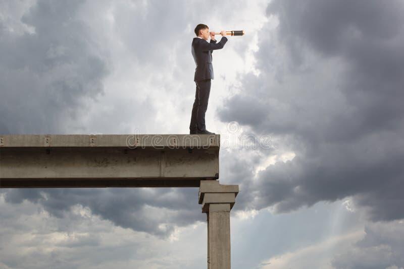 El hombre de negocios mira a través de un telescopio fotografía de archivo
