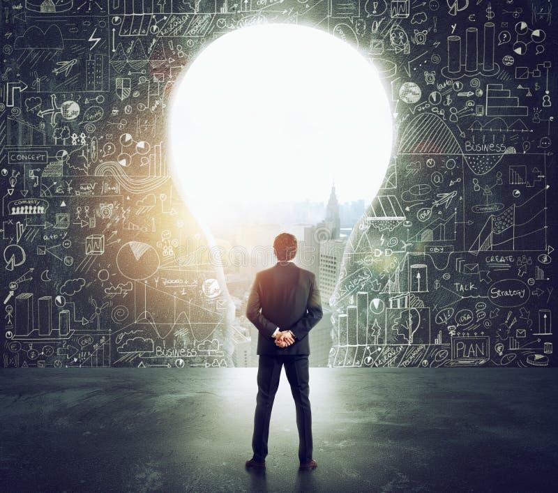 El hombre de negocios mira un agujero grande en la pared formada como bombilla foto de archivo libre de regalías