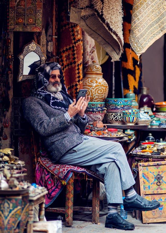 El hombre de negocios de moda se sienta en mercado de la ciudad con el vestido tradicional de la muselina, Marrakesh, Marruecos fotografía de archivo libre de regalías