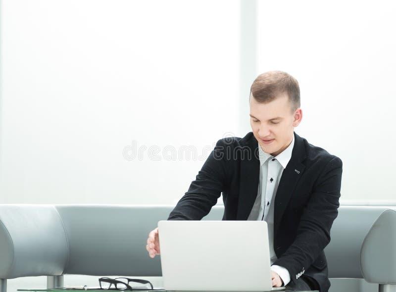 El hombre de negocios moderno utiliza un ordenador portátil en el pasillo del hotel imagen de archivo