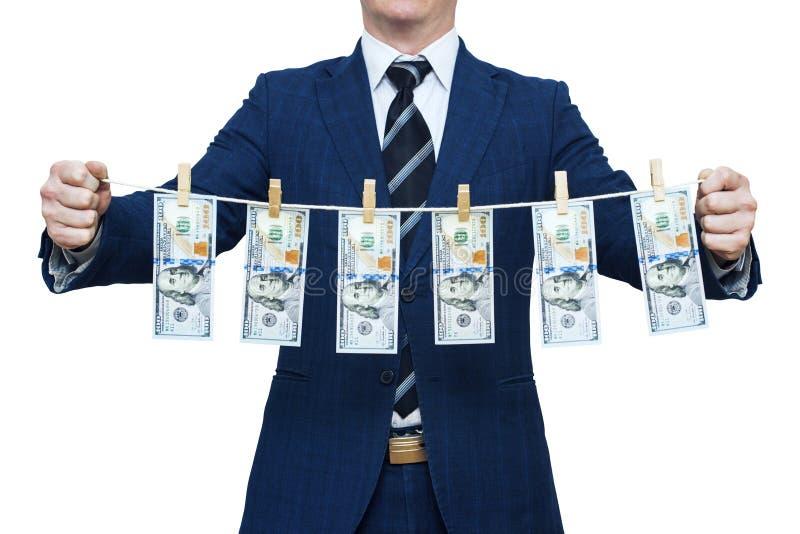 El hombre de negocios muestra el dinero lavado planchado Hombre de negocios que sostiene el dinero que cuelga en una cuerda imagen de archivo